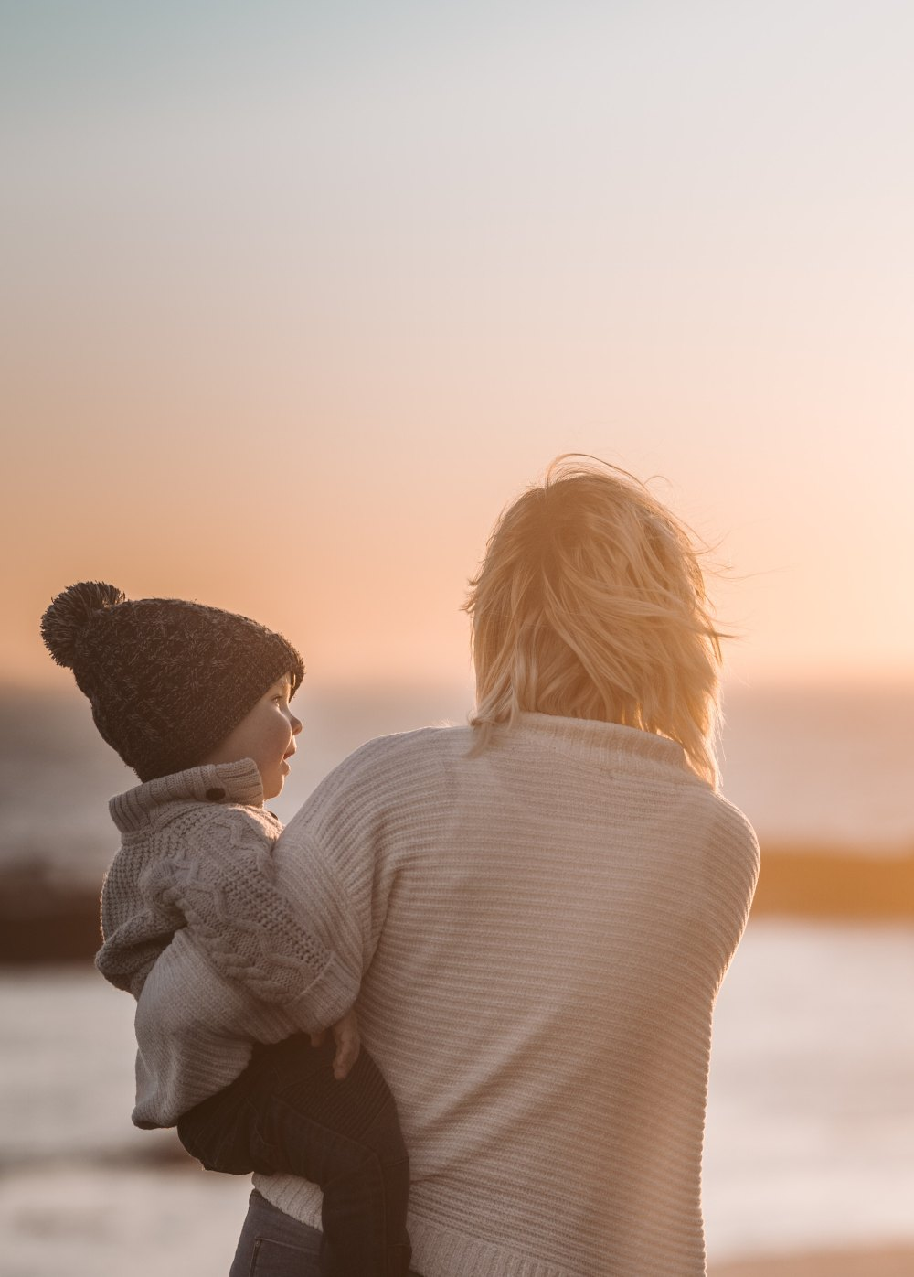 mother stares out to sunset with child in her arms